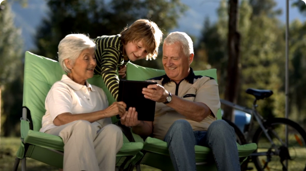 A kid showing tablet to two senior citizens